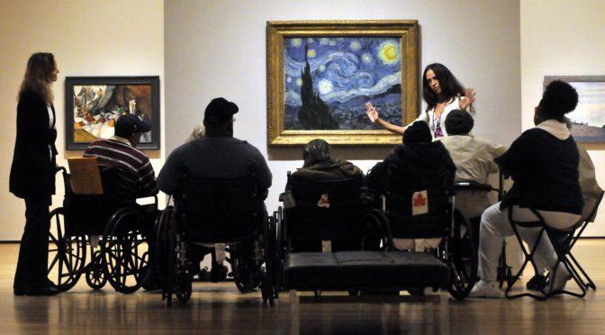 Eine Frau gibt ein ausdrucksvolles Gespräch für eine Gruppe von Menschen in Rollstühlen und auf Hockern in einer Galerie vor Van Goghs Gemälde Starry Night. A woman gives an expressive talk for a group of people in wheelchairs and on stools in a gallery in front of Van Gogh's The Starry Night.