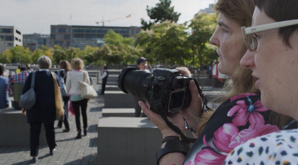 Zwei Frauen schauen über die Berliner Holocaust-Gedenkstätte. Eine beschreibt die Szene dem anderen, der eine digitale Spiegelreflexkamera in den Händen hat. Two women look out over the Berlin Holocaust memorial. One describes the scene to the other who has a digital SLR camera in her hands.