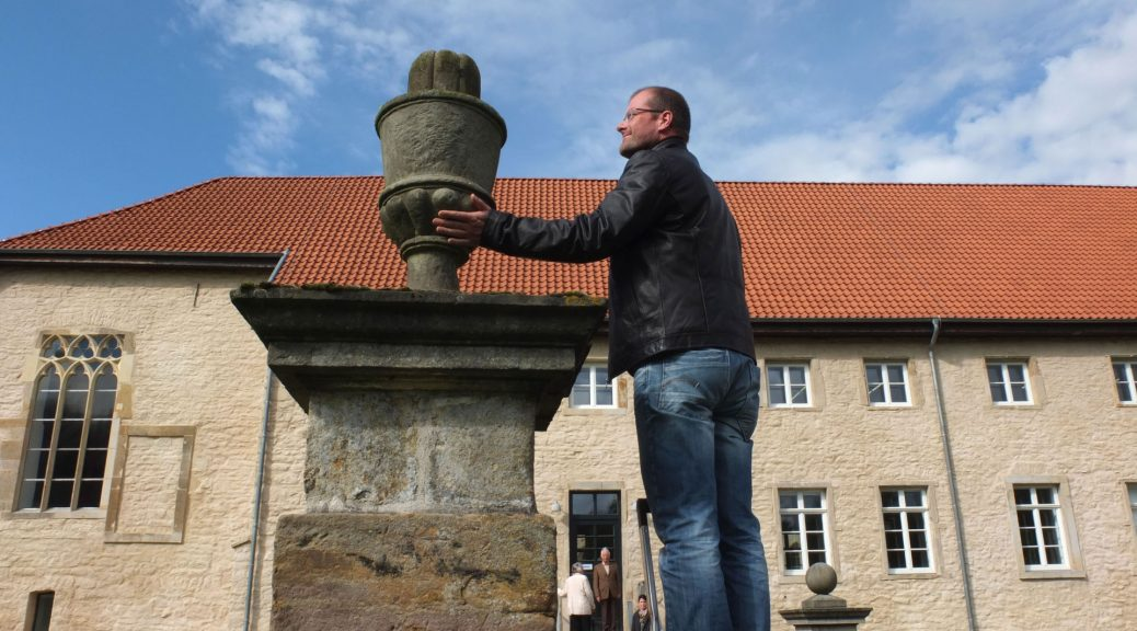 Ein lächelnder Man berührt ein Steinkkulptur. A smiling man touches a stone sculpture.