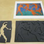 A copy of Henri Matisse's The Dance lies on a table above a relief of that image, made out of foam core. On the left of the relief is a cut-out of one of the figures from the image.