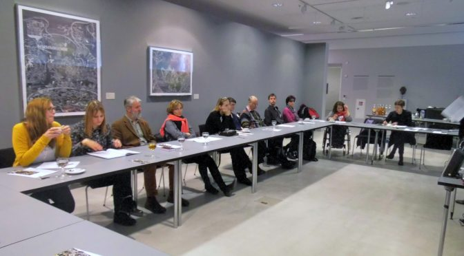11 people sit around a large table in a workshop room in a gallery listening to a presentation.