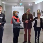 Two people wearing simulation spectacles are guided through a gallery by a sighted person.
