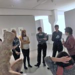 A group of people listen to a blind woman talking in a gallery.