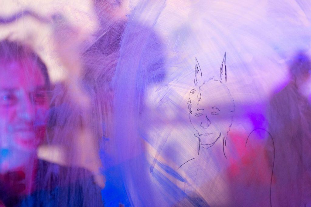 Person, die eine Zeichnung auf einer Glasoberfläche betrachtet