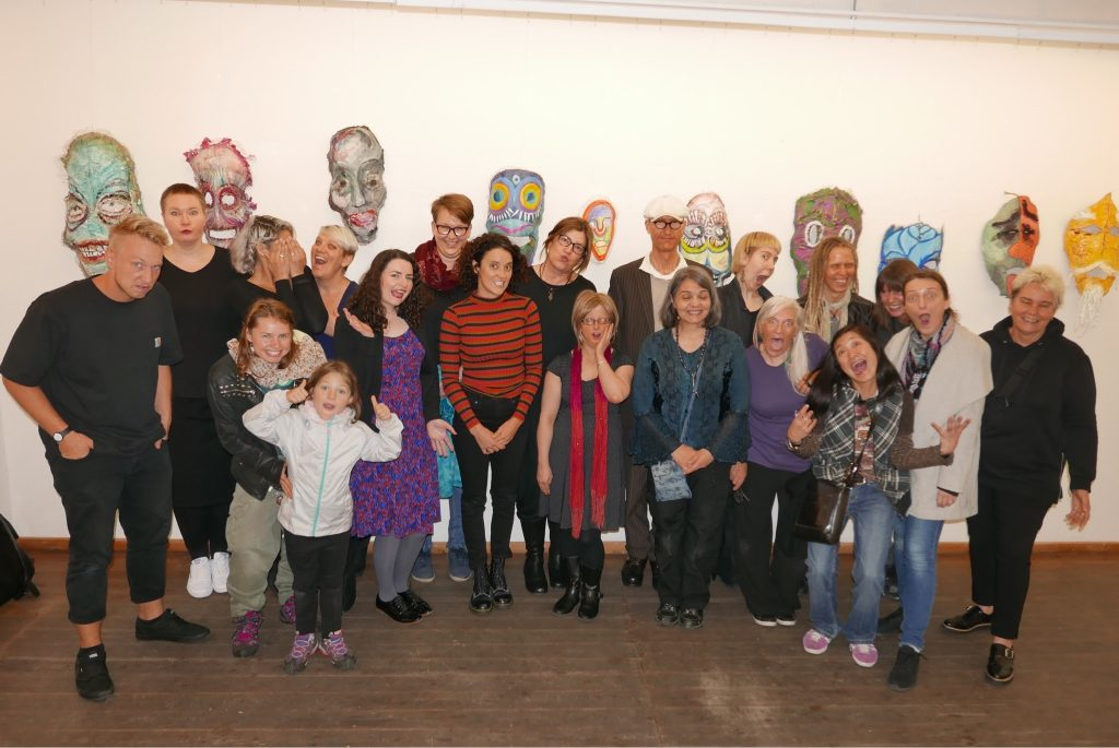 Group photo with colorful masks in the back wall