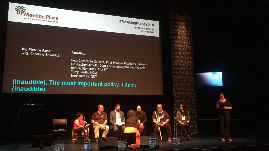 Menschen mit und ohne Behinderungen diskutieren auf der Bühne während eines Symposiums