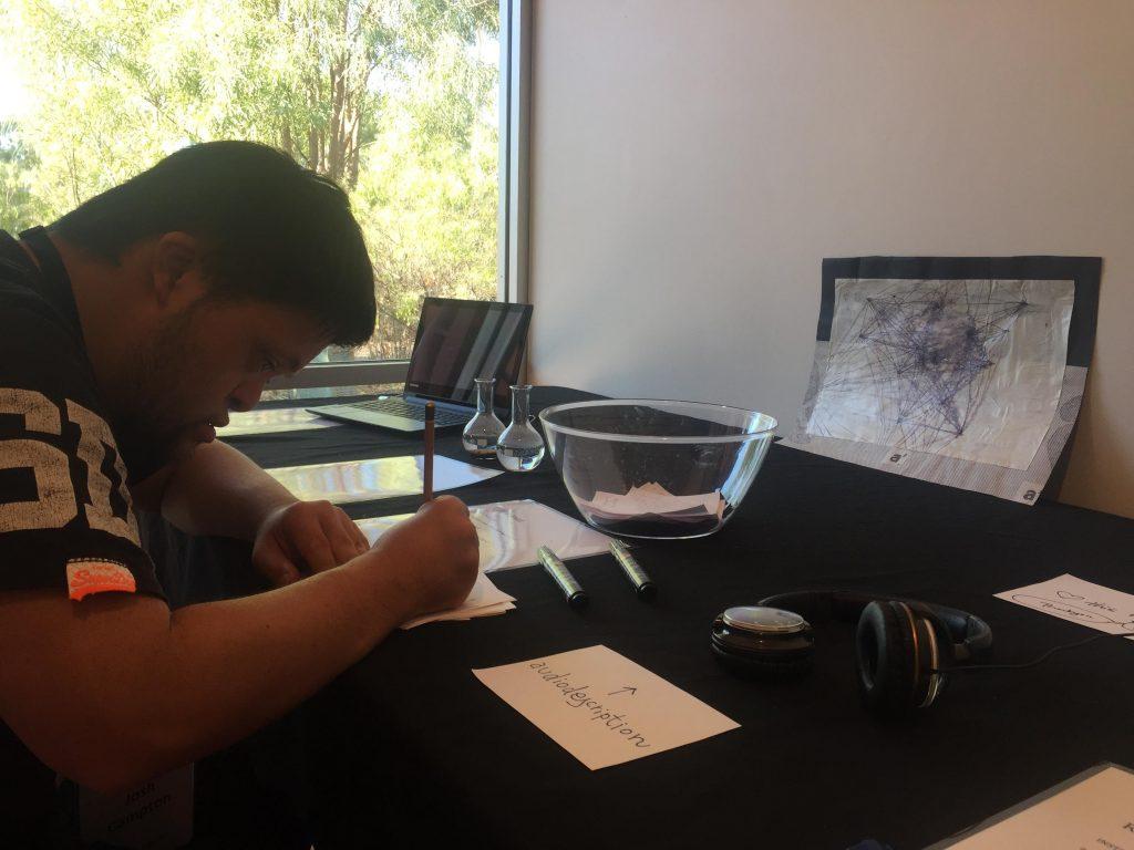 Eine Person schreibt auf einen Tisch, auf dem sich ein Laptop, eine Glasvase, 2 Glasampullen, ein Paar Headsets, eine Zeichnung und 2 weiße Flugblätter befinden