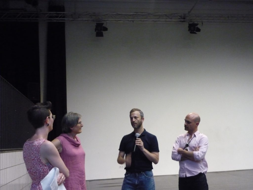 Three people on the stage presenting the event