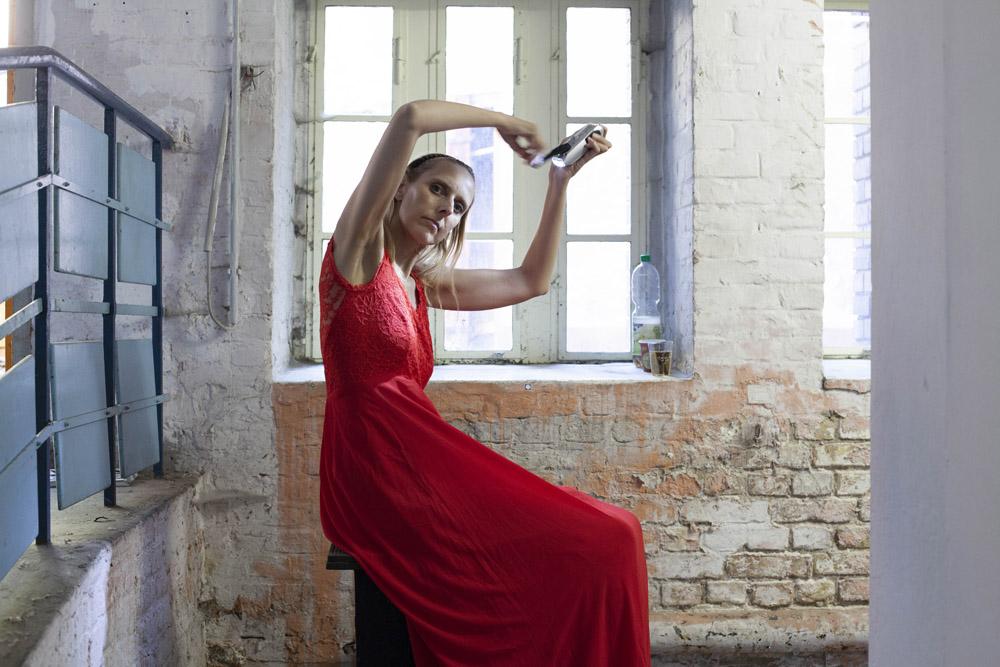 Eine Performerin im roten Kleid auf Sockel sitzend hält eine Taschenlampe in den Händen und leuchtet sich an.