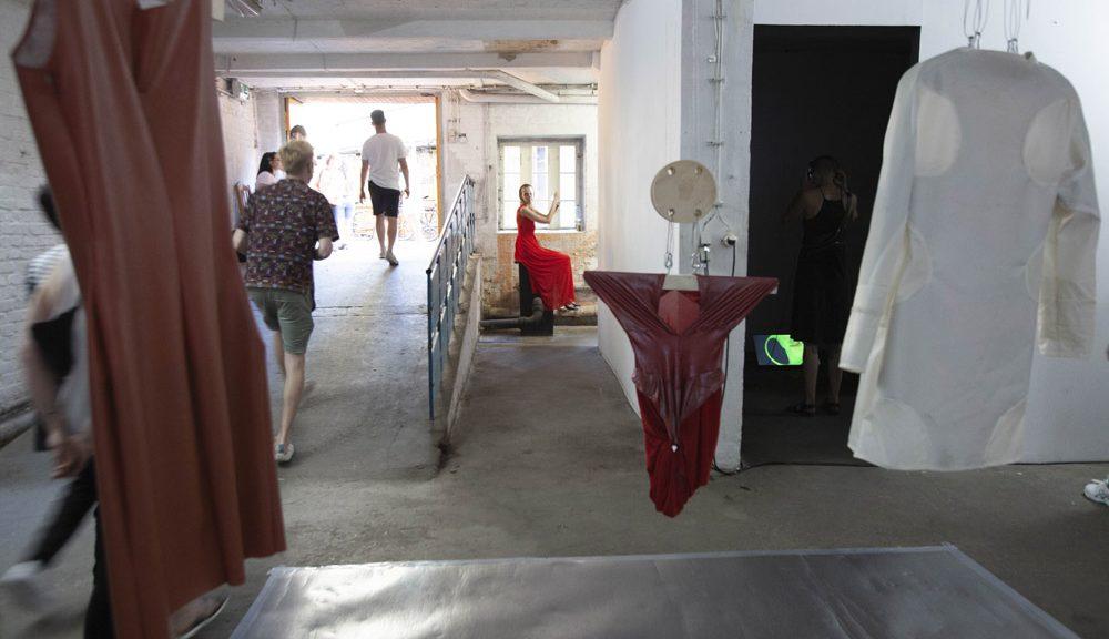 Blick in Ausstellung: Im Vordergrund hängen Kleider von der Decke. Im Hintergrund Menschen auf einer Rampe und Performerin im roten Kleid auf Sockel sitzend.