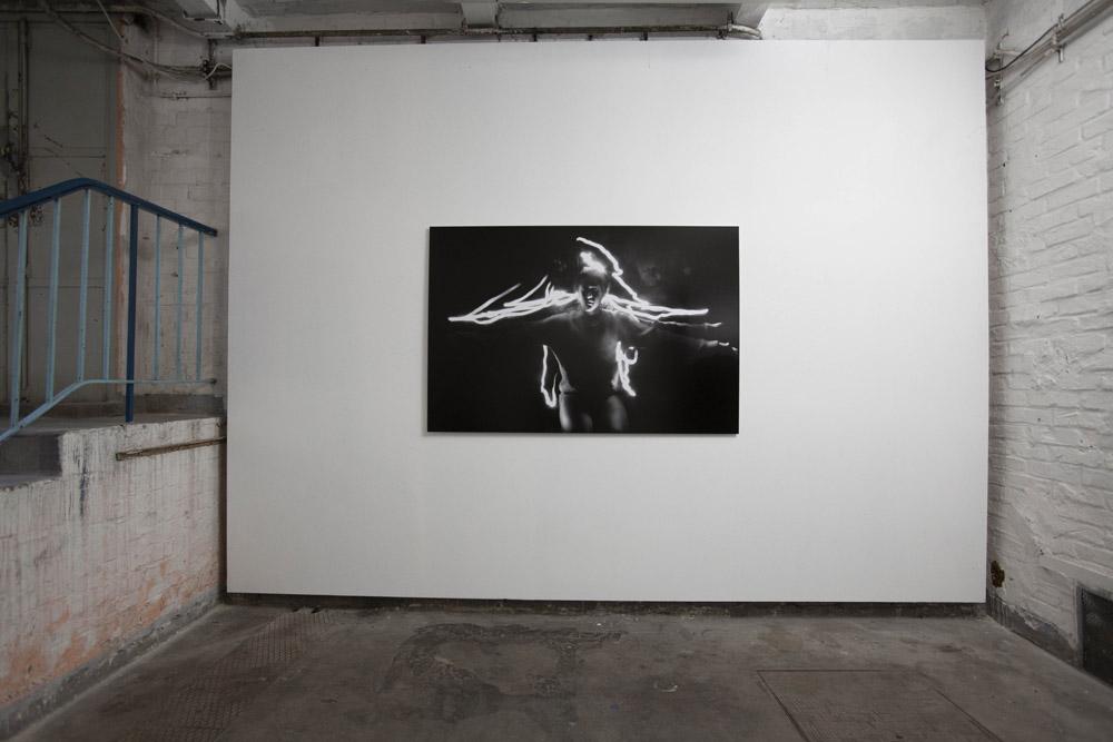 Schwarz-Weiß-Foto im Querformat an einer weißen Wand. Kniende Frau mit ausgebreiteten Armen.