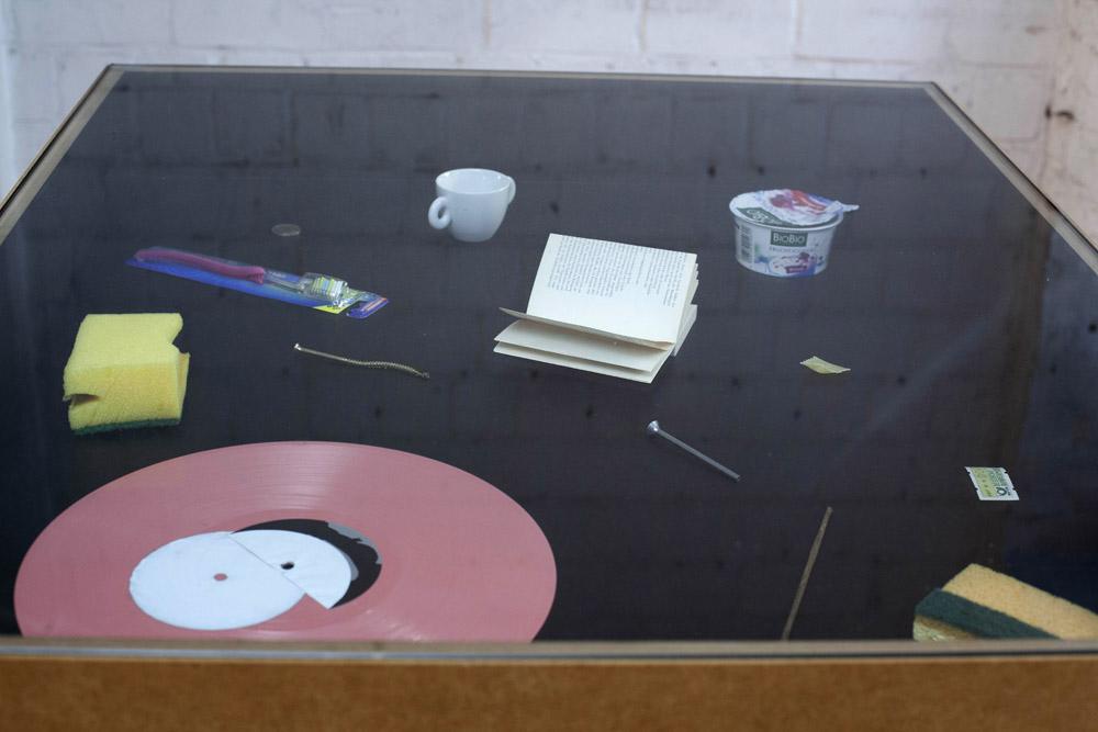 Verschiedene Objekte in einer Tischvitrine: eine Schallplatte, zwei Schwämme, zwei Schrauben, eine Briefmarke, eine Espressotasse, etc.